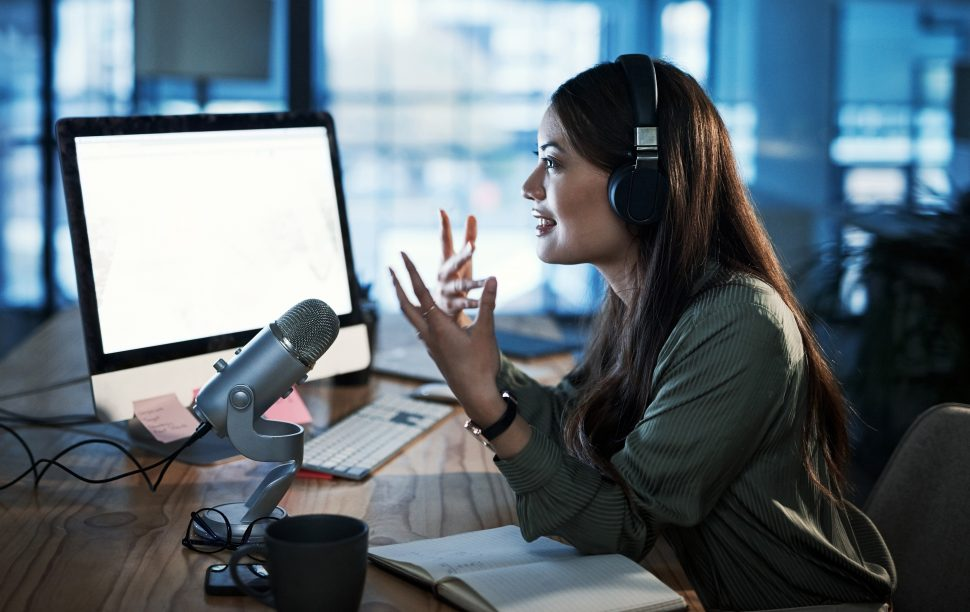 Woman sitting at a desk podcasting with headphones on and microphone in front of her.