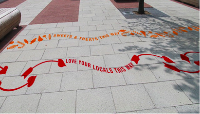 """street decals stating """"love your locals this way"""" directing passerby to a location as a form of guerrilla marketing"""